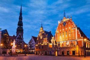 Riga Town Hall Square, House of the Blackheads, St. Roland Statue and St. Peter's Church illuminated in the evening, Riga, Latvia